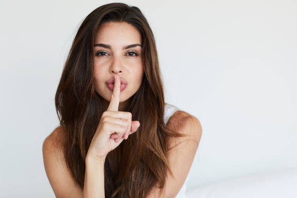 Secrecy girl Beautiful brunette with a secret, portrait finger on lips stock pictures, royalty-free photos & images