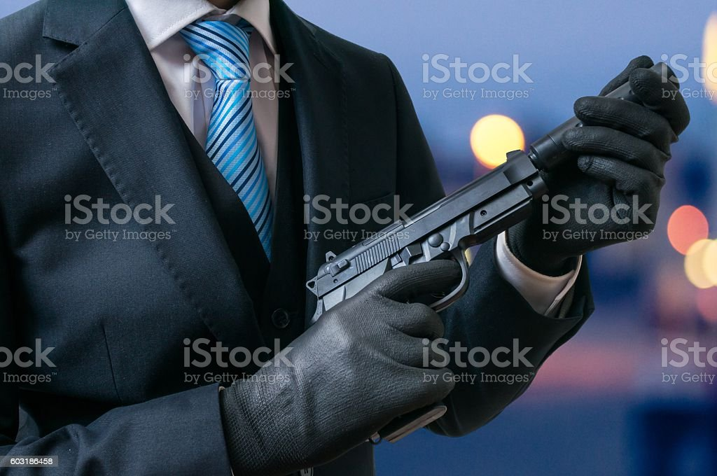 Secret agent holds pistol with silencer in hands at twilight. stock photo