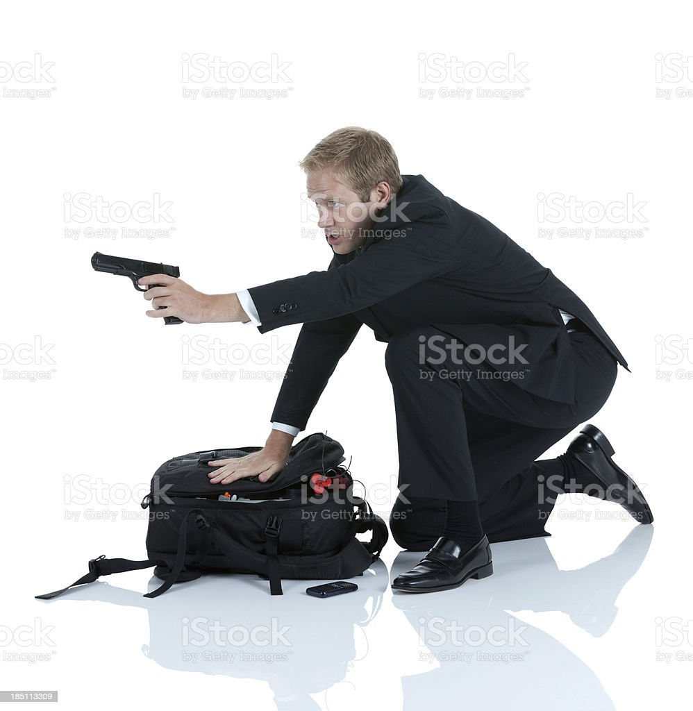 Secret agent near bag of explosives and aiming with handgun royalty-free stock photo