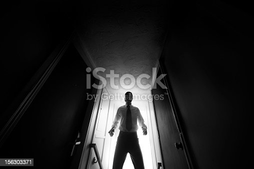 A spy or undercover agent enters the corridor hallway of a dark hotel, gun in hand.  Horizontal with copy space; black and white.  GRAIN ADDED.