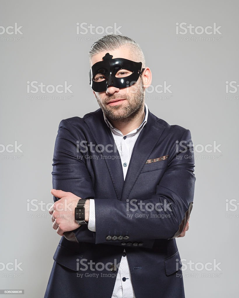 Secret. Elegant bearded man wearing carnival mask Portrait of elegant bearded businessman wearing jacket and carnival mask. Standing against grey background with arms crossed and looking at camera. Studio shot, one person.  Adult Stock Photo