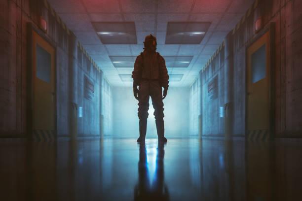 secret government underground facility with standing man in hazmat suit - conspiracy стоковые фото и изображения