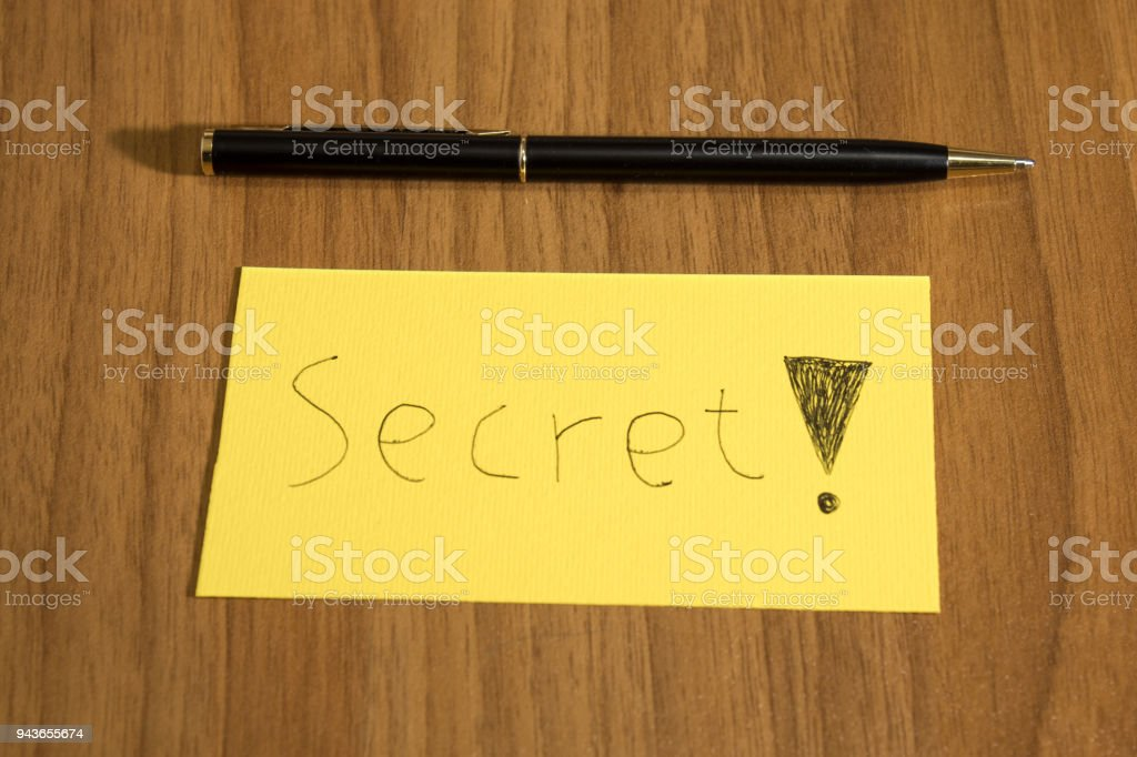 Secret handwrite on a yellow paper with a pen on a table composition stock photo