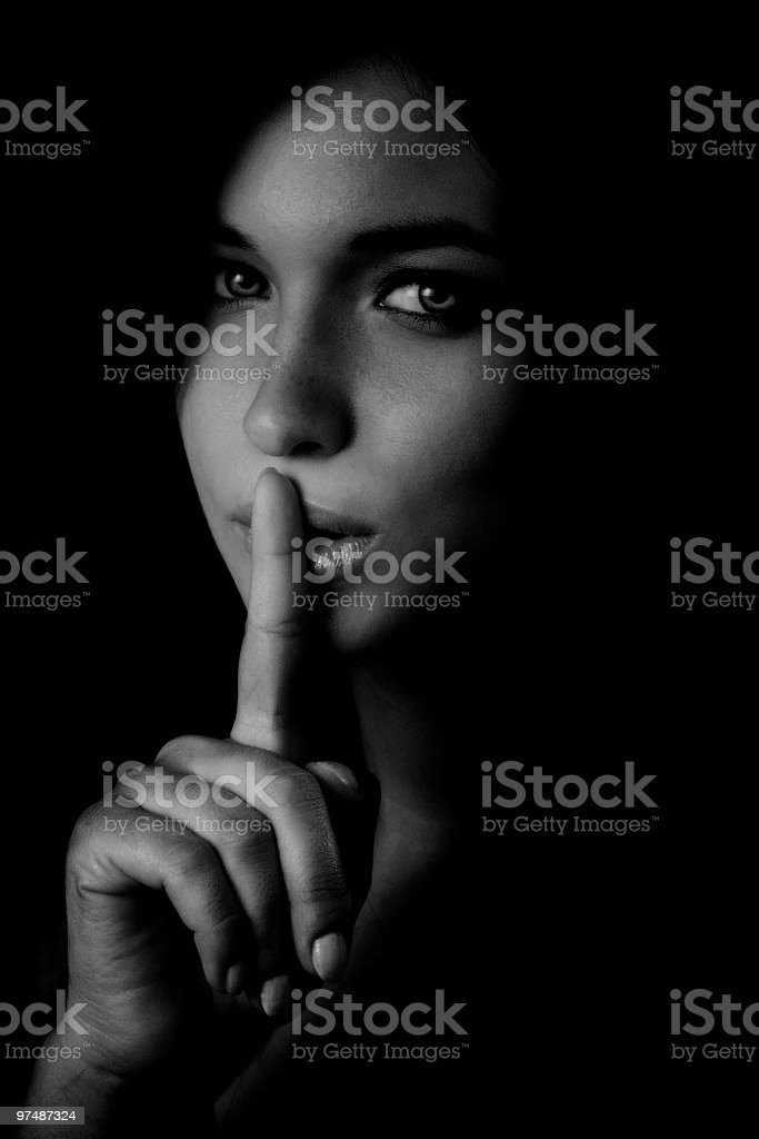 Secret - mystery woman with finger at lips stock photo