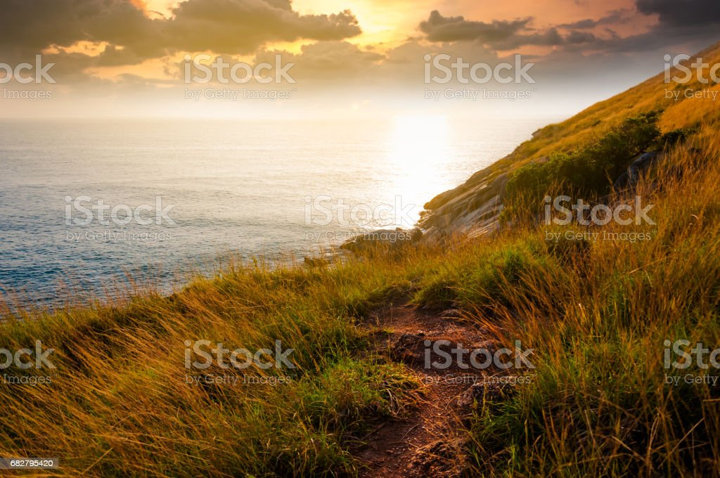 A secret pathway to beautiful scenic unknown cliff during sunset nearby Naiharn beach in Phuket Thailand stock photo