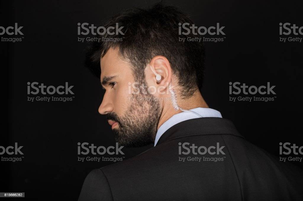 Secret service agent in suit using earphone, isolated on black stock photo