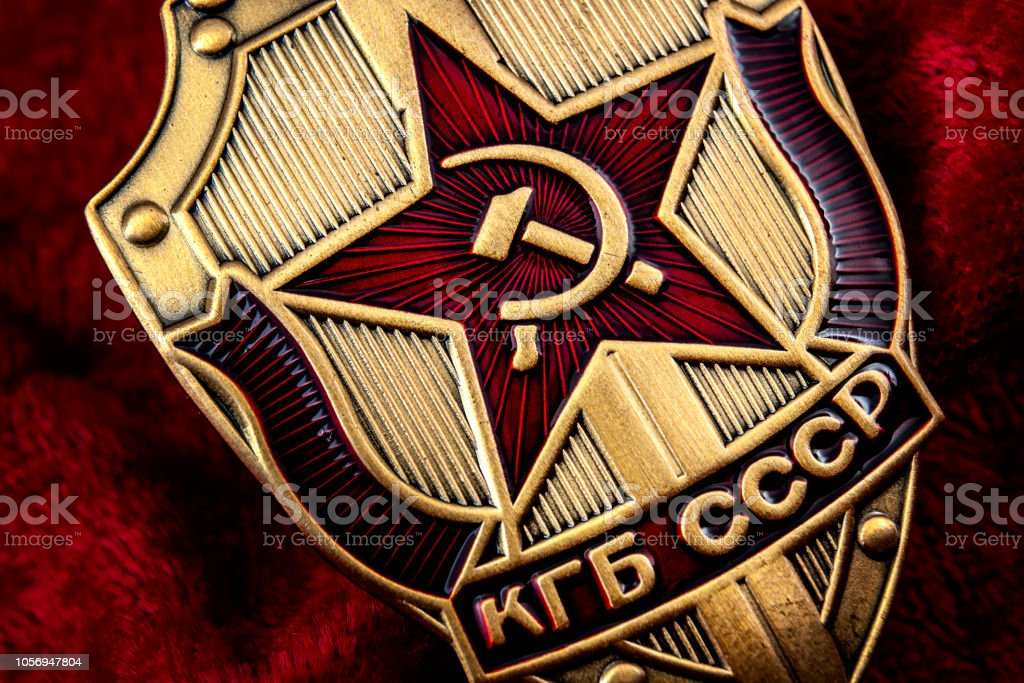 Secret service, intelligence agency, and espionage concept with macro close up on a cold war era KGB badge from the former USSR on red background stock photo
