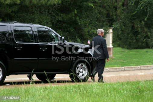 Black SUV with security guards walking alongside.  Motorcade.