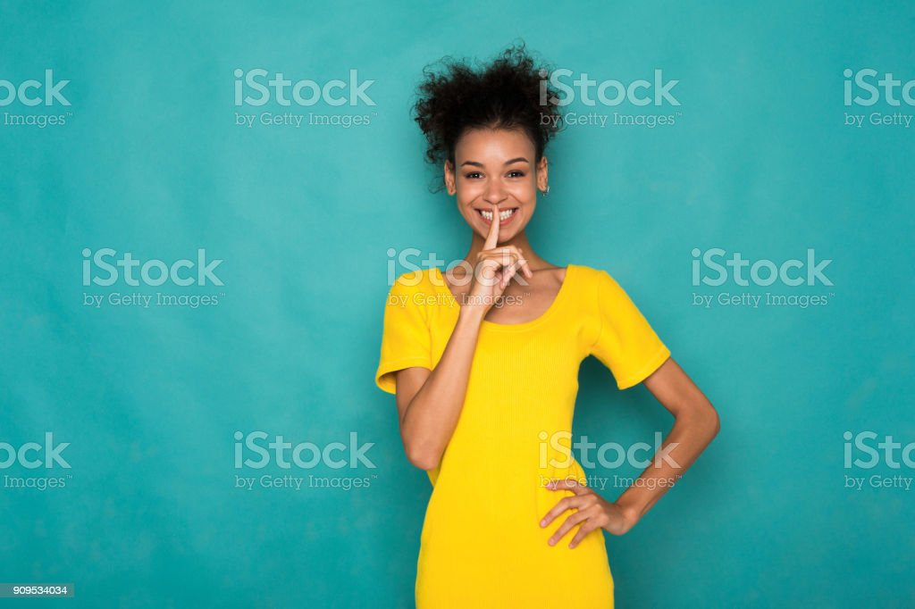 Secret. Young woman put finger on lips, hush sign stock photo