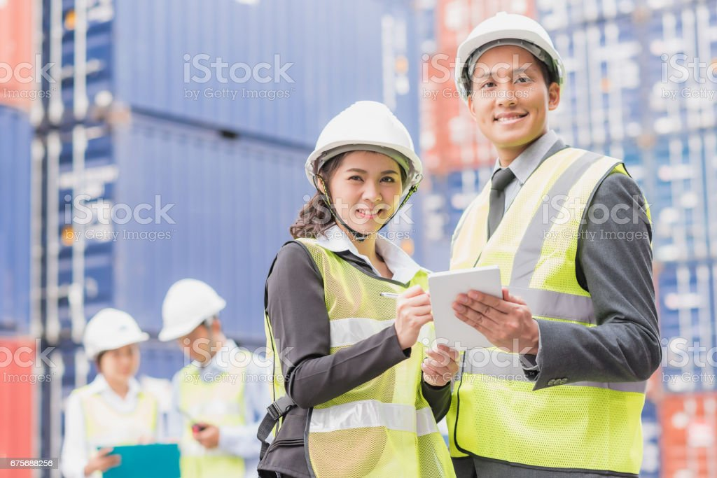Secretary and businessman with shipping cargo container freight in background. stock photo
