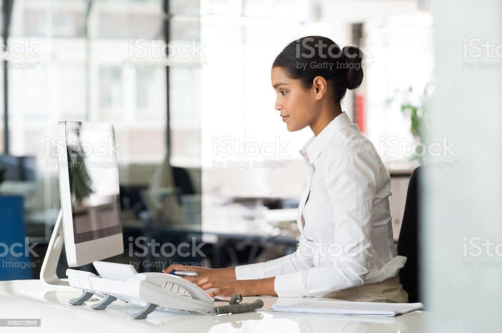 Secretary at computer desk stock photo