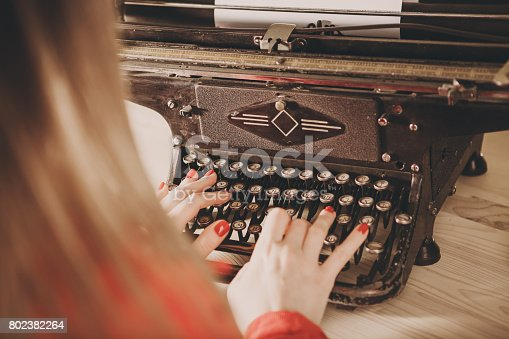 istock Secretary at old typewriter with telephone. Young woman using typewriter. Business concepts. 802382264