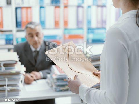 istock Secretary bringing an envelope to her boss 916425402
