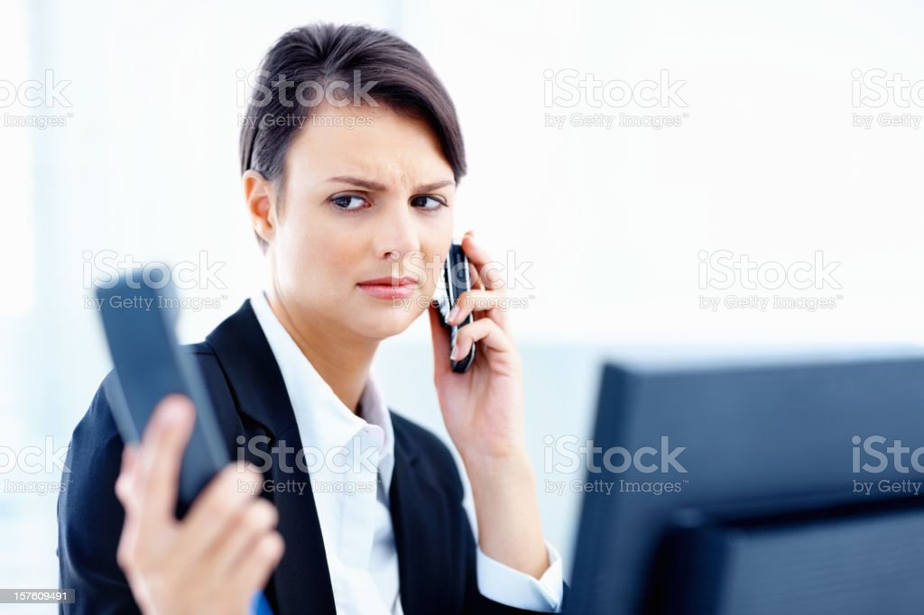 Secretary holding telephone handset and cellphone at work royalty-free stock photo