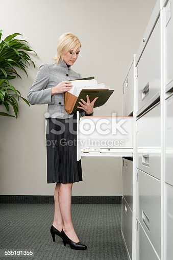 535191355istockphoto Secretary looking at files 535191355