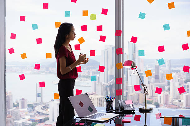 secretary organizing tasks writing sticky notes on window - household chores stock photos and pictures