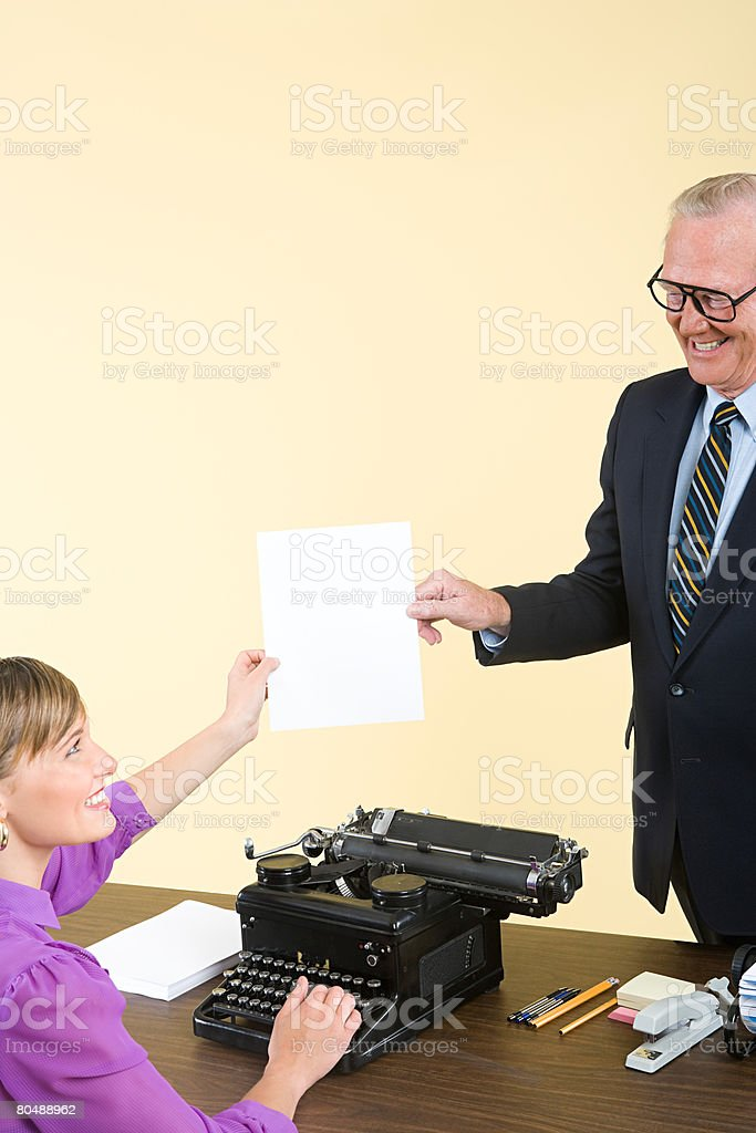 A secretary passing a businessman a document royalty-free stock photo