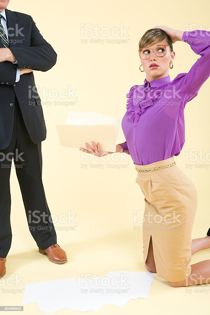 A secretary picking paperwork up off the floor royalty-free stock photo
