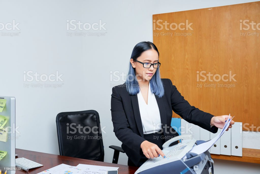 Young Asian businesswoman with blue hair printing out document via...