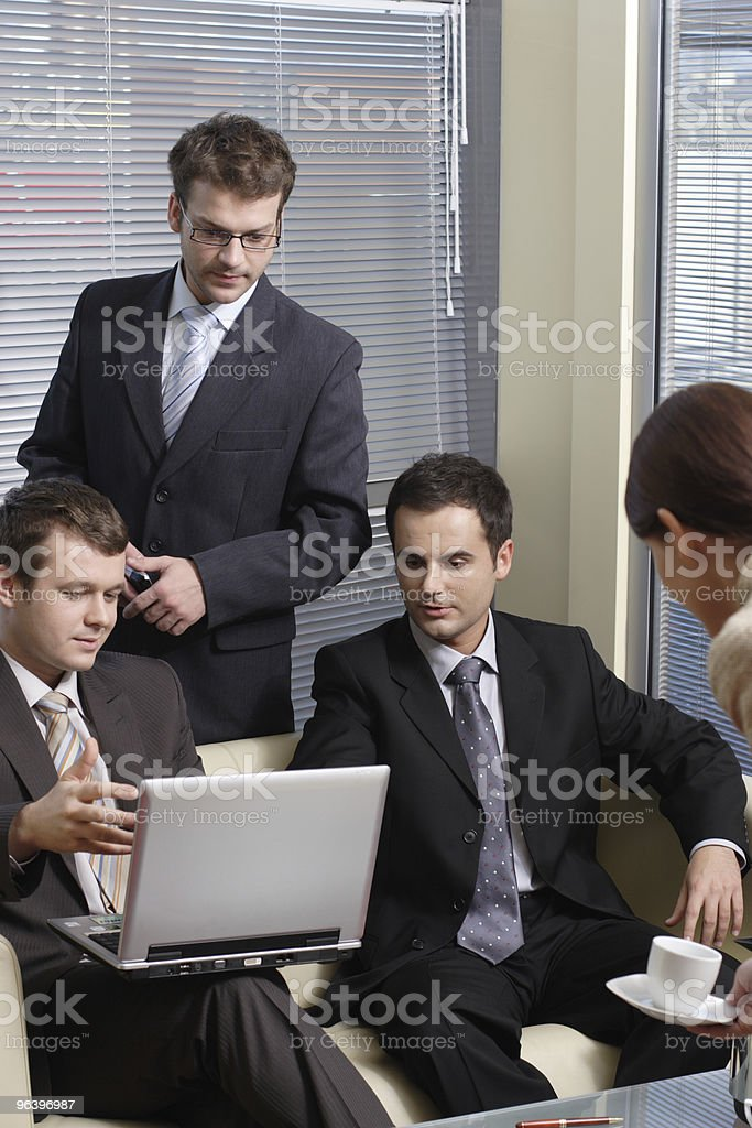 Secretary serving cup of coffee to young business men - Royalty-free Adult Stock Photo