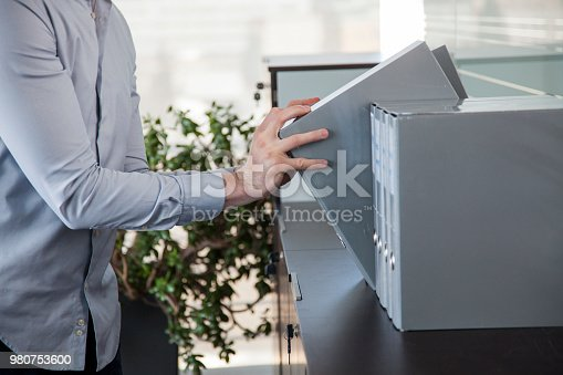Ring binders on a shelf of a modern office with plan and window in the background. Secretary taking one.
