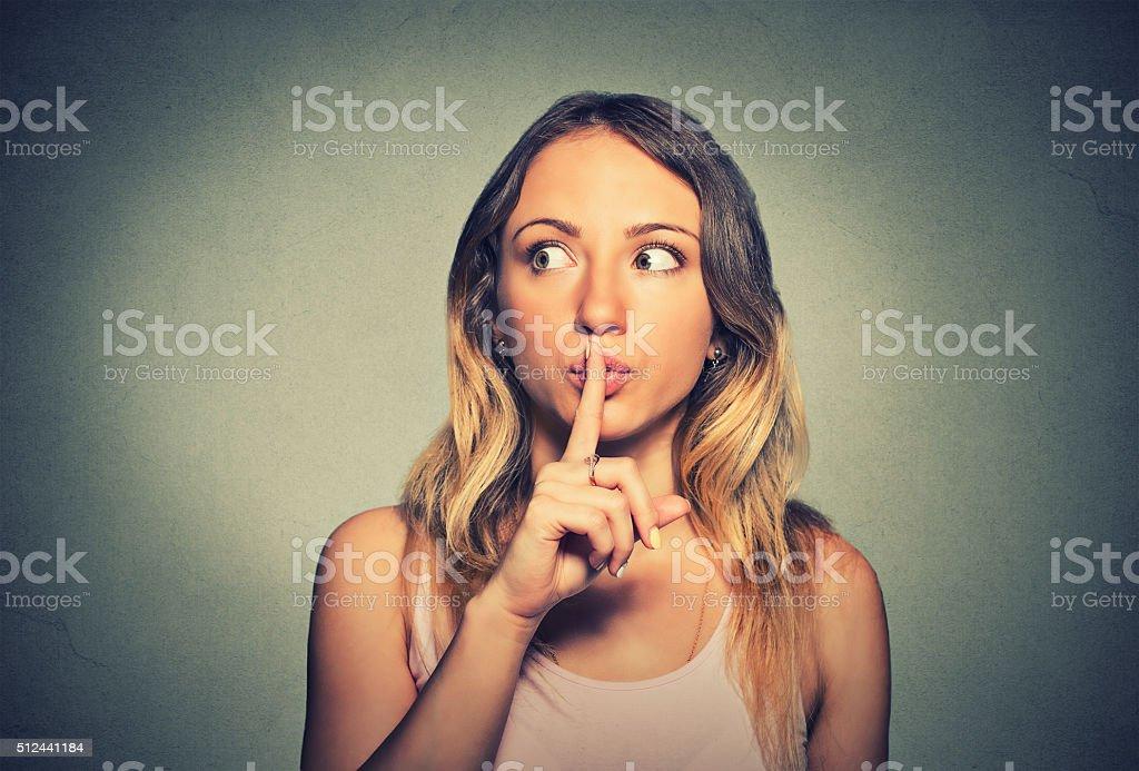 secretive woman placing finger on lips shh, quiet stock photo
