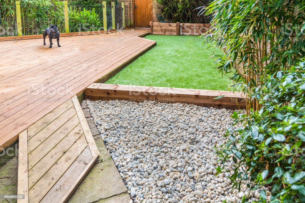 A section of a residntial garden, yard with wooden decking and artificial grass stock photo