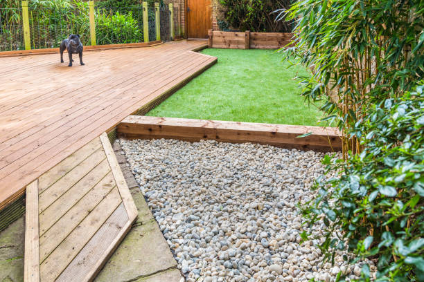 a section of a residntial garden, yard with wooden decking and artificial grass - imitation stock photos and pictures