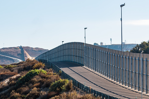 A section of the international border wall between San Diego, California and Tijuana, Mexico, as it travels over rolling hills.