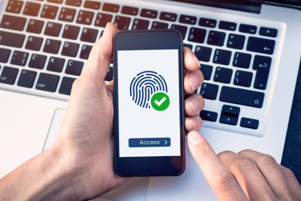 secure access granted by valid fingerprint scan, cyber security on internet with biometrics authentication technology on mobile phone screen, person holding smartphone connected with wifi - convalida foto e immagini stock