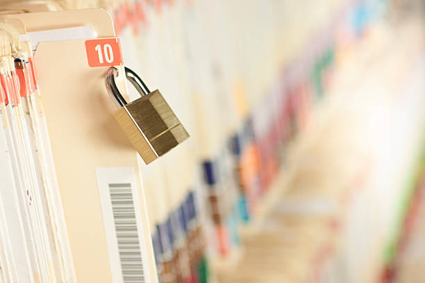 Secure Medical Records Secure and protected medical records. Bar code added to folder, not actual patient information. Concept image. Narrow depth of field. privacy stock pictures, royalty-free photos & images