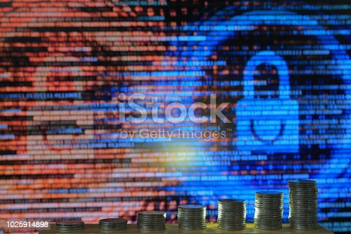 istock secured internet business. big coin piles in front of blue binary code computer screen. rich through savings account online. 1025914898