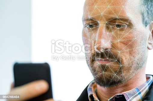 Man holding his smartphone up to his face to verify his identity (ID) with biometric facial recognition software. Facial recognition is a system whereby a user's face is scanned to verify his or her identity.