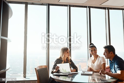 Shot of a young couple meeting with a financial planner in a modern office