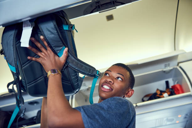 Securing my luggage Shot of a young person in an airplane carry on luggage stock pictures, royalty-free photos & images