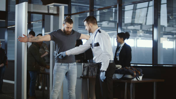 Security agent patting down a male passenger Security agent at an airport check-in gate patting down a bearded casual male passenger with outstretched arms after he passes through the metal detector scanner in the departures hall. security staff stock pictures, royalty-free photos & images