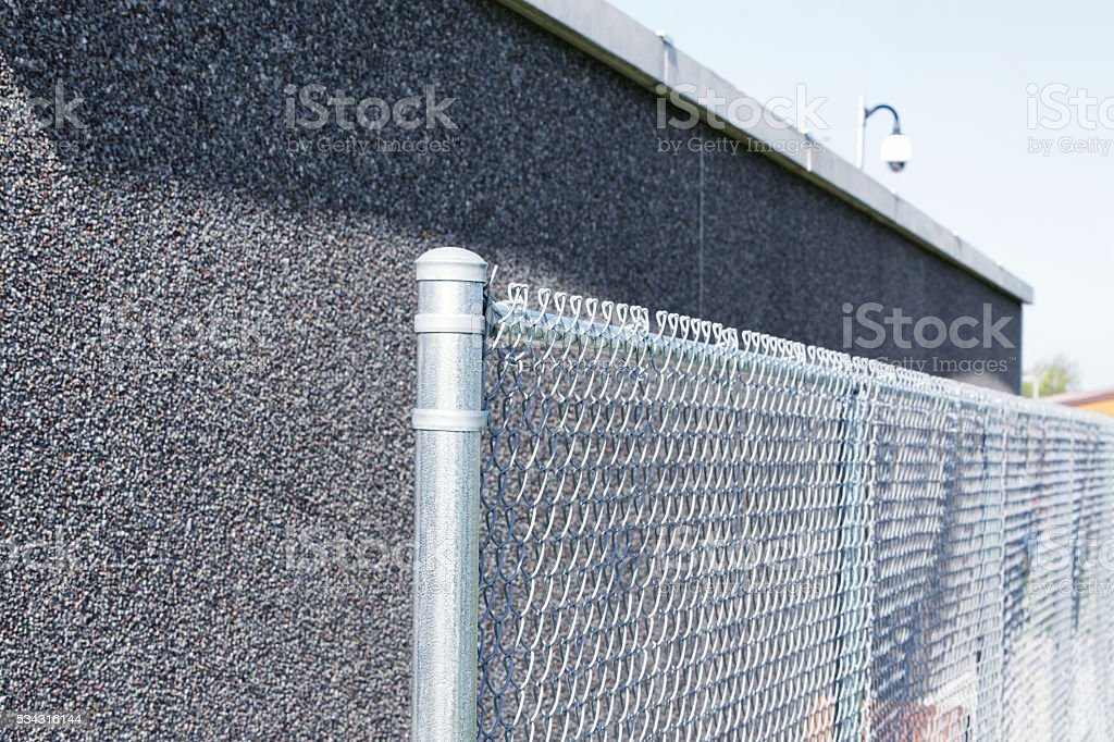 Security Camera Above Baseball Diamond Dugout Chainlink Fence stock photo