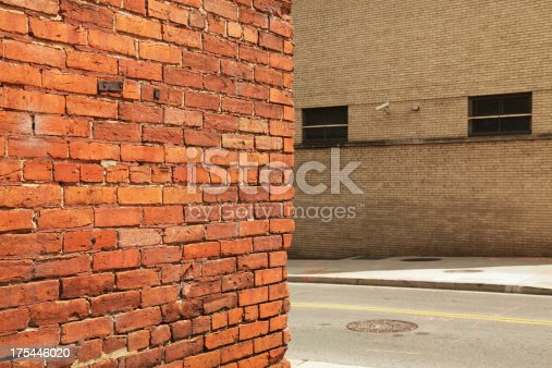 The corner of an old brick wall with a newer, grungy brick wall across a city street featuring a security camera mounted high above the sidewalk. Nashville, Tennessee, U.S.A.