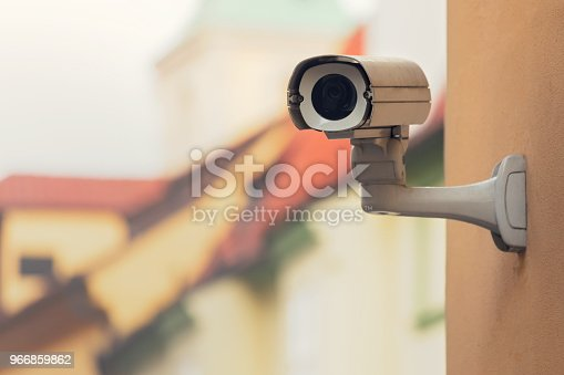 A security camera on an apartment building wall in a city environment.