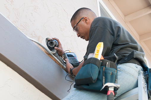 A technician uses a monitor to adjust a security camera while installing the system to the exterior of a building.