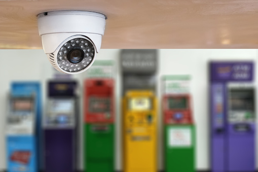 istock security camera or cctv camera surveillance installed on the building wall at atm bank machine. 953843130