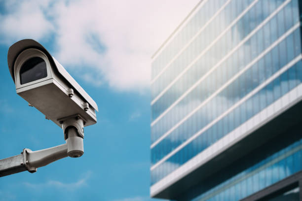 Security camera with a glass building on the background stock photo