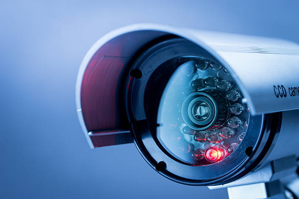 Security CCTV camera in office building Security, CCTV camera for office building at night in London. security stock pictures, royalty-free photos & images