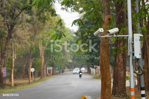 istock Security CCTV camera installed  at public area near road over blur transport background for security concept 943029104