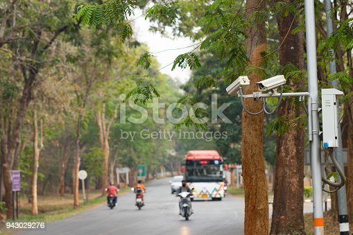 istock Security CCTV camera installed  at public area near road over blur transport background for security concept 943029276