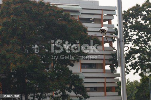 istock Security CCTV camera installed  at public area near road over blur transport background for security concept 954022398