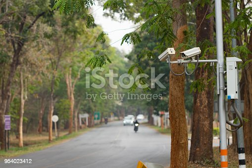 istock Security CCTV camera installed  at public area near road over blur transport background for security concept 954023412