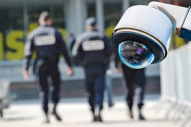 security CCTV camera or surveillance system with military on blurry background stock photo