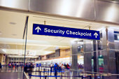 Airport Sign at the entrance of the security checkpoint with People waiting in line.