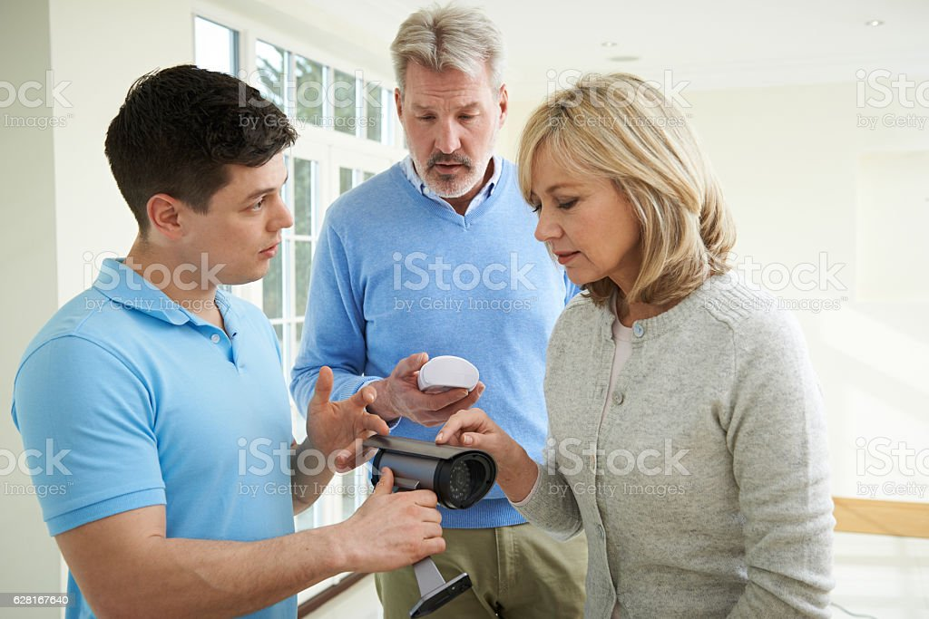 Security Consultant Demonstrating Alarm System To Mature Couple stock photo